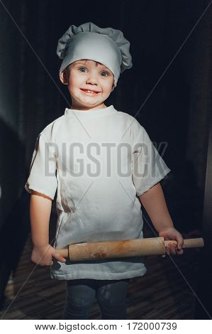 Baby cook with a rolling pin on a black background
