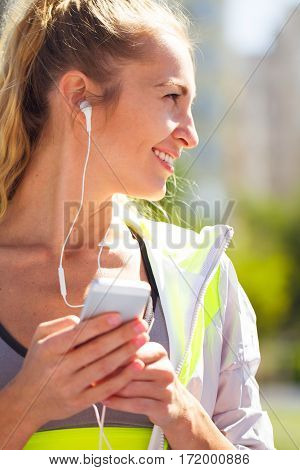 Portrait Beautiful Young Woman With Phone In Earphones. Sport At Stadium.
