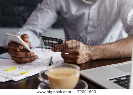 Close Up Shot Of African Man's Hands Holding Mobile And Credit Card. Dark-skinned Businessman Checki