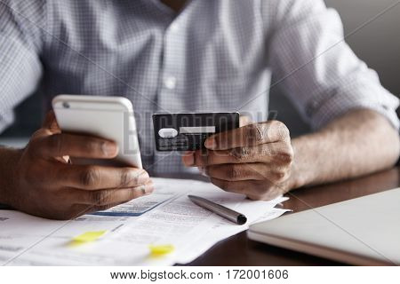 Cropped Shot Of African-american Male Paying Bill At Restaurant With Online Payment Technology Via I