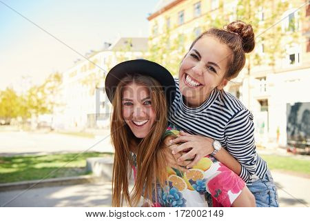 Two Happy Young Women Friends Piggy Backing
