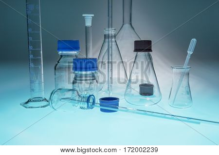 Glass laboratory apparatus isolated on blue table