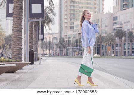 Young blond woman in blue blouse white trousers yellow shoes and with green handbag standing at Dubai street. Female with trendy make up and long blond hair standing near road with a smile