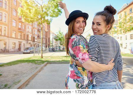 Happy Friendly Young Women Walking Arm In Arm