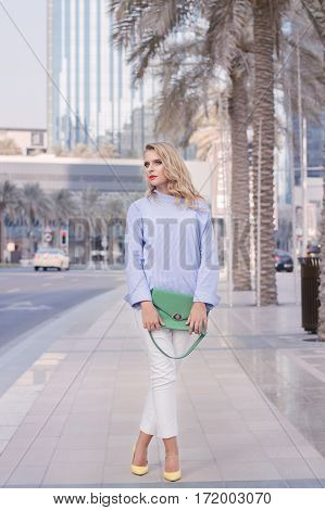 Elegant young female with blond curly hair and trendy make up with red lips standing near road under palm trees in Dubai UAE. Young business woman