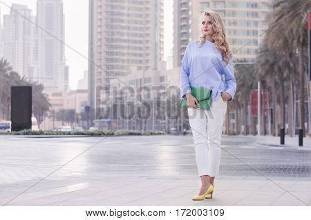 Young european woman with curly blond hair and trendy make up standing near empty road in Dubai downtown UAE. Stylish business woman in blue blouse white trousers yellow shoes and green handbag