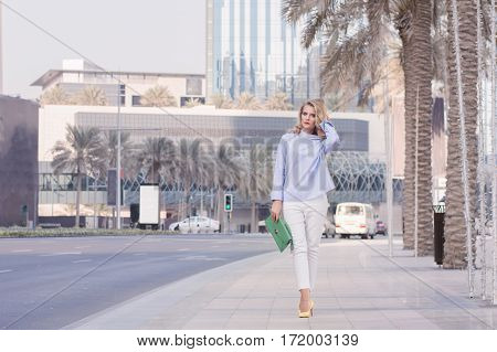Stylish blond woman in smart casual blouse and white trousers holding a green handbag. Young female walking through empty street in Dubai Downtown UAE