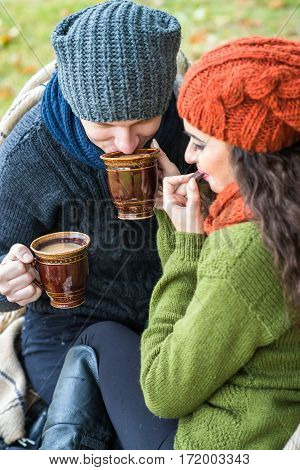 couple in love drinks coffee in the autumn garden
