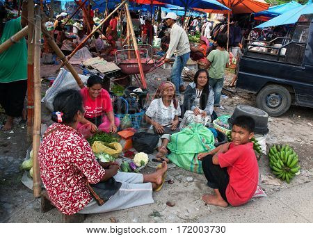 PARAPATINDONESIA - AUGUST182012: Women and boy sell vegetables at the market near the pier