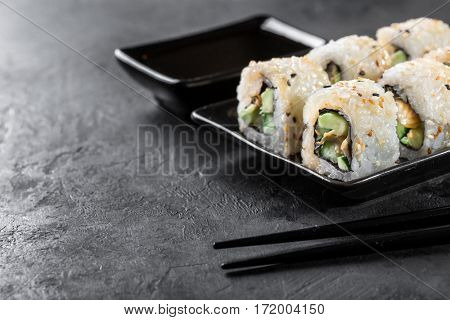 sushi roll with chopsticks and soy on a dark background