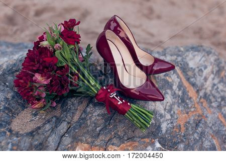Red women's shoes with red wedding bouquet close-up
