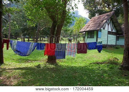 Laundered linens is dried in the garden near the house