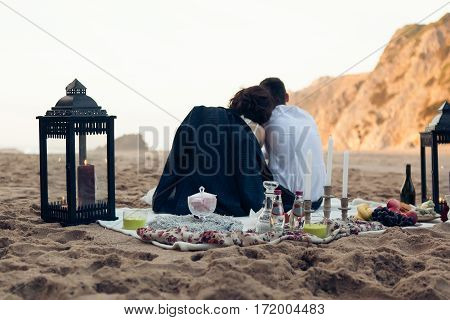 Loving couple on a romantic date at the beach sunset