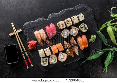 Sushi Set sashimi and sushi rolls served on stone slate