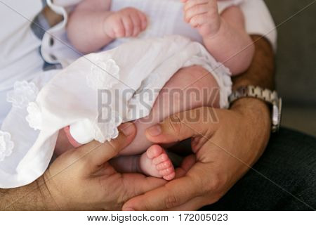 Father holding a small daughter in dress close-up