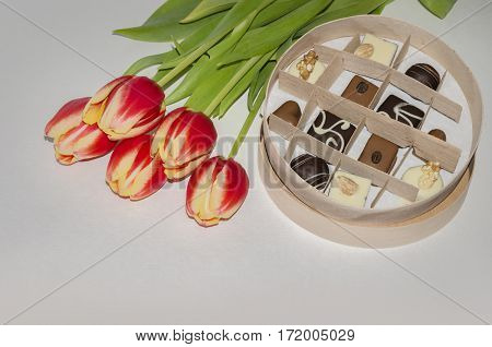 box of chocolates for the holiday and red tulips closeup