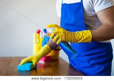 Closeup Of Young Man Wearing Apron Cleaning Kitchen Worktop