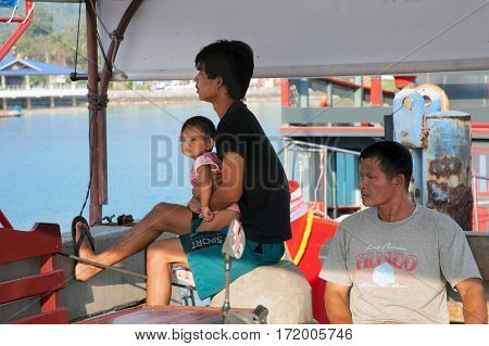 SAMUI THAILAND - JANUARY 202011: Two Thai men and a boy waiting for a ship at the pier