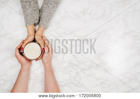 Couple in love holding hands with coffee on white marble table. Photograph taken from above, top view with copy space