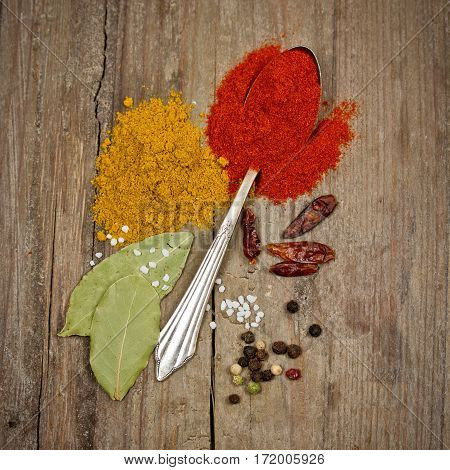 some spices with spoon on wooden table