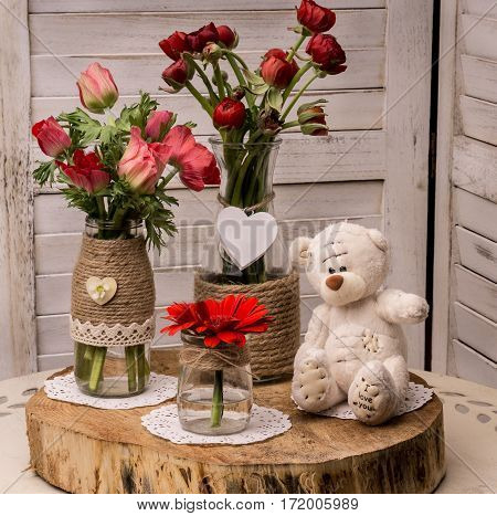 Composition of several bouquets of flowers in red and soft teddy bear