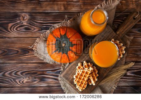 Bottle And Glass Of Healhty Fresh Pumpkin Juice With Wafer And Pumpkin On Dark Wooden Table. Selecti