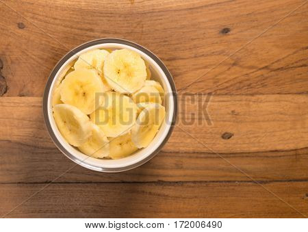 Aerial or top view of a white glass bowl of organic banana slices freshly washed and sitting on old wood table surface