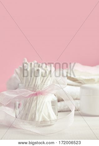 White cotton swabs in glass jar with ribbon bow decor, pink background. Feminine beauty care. Vertical set. Soft light and focus. poster