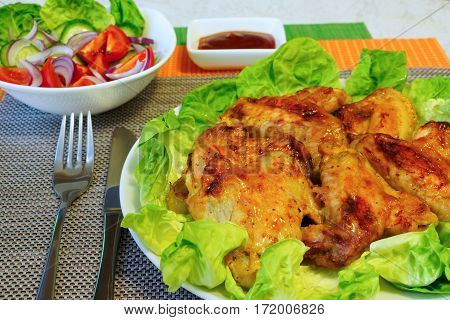 Grill wings on lettuce leaves. Vegetable salad in a white salad bowl. Ketchup in a gravy boat. Table setting.