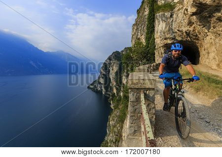 View of cyclist riding mountain bike on trail Sentiero Ponale in Dolomites,Tre Cime di Laverado, South Tirol, Italy