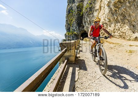 Mountain biking woman over Lake Garda on path Sentiero della Ponale, Riva del Garda, Italy