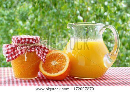 Orange juice jam orange halves on a red checkered tablecloth.