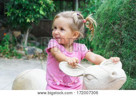 Little Girl Rides A Toy Deer