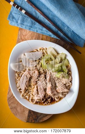 Soup noodle ramen c celery chicken daikon on a yellow table vertical