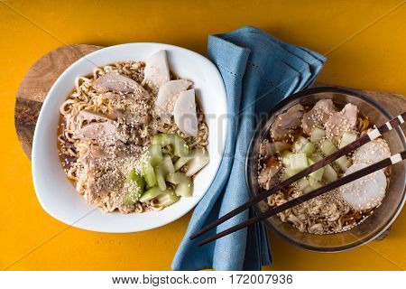 Two bowls of soup noodle ramen celery chicken on a yellow table horizontal