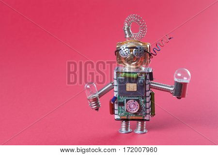 Robot concept retro style. Circuits socket chip toy mechanism funny head eyes glasses light bulbs in hands. Copy space pink background