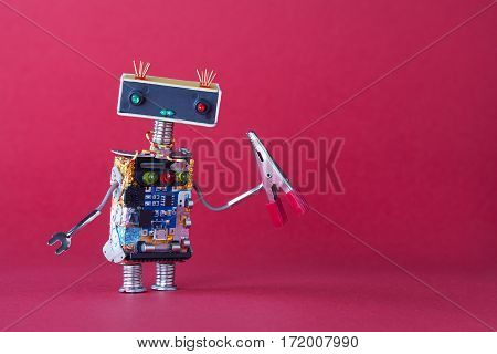 Friendly Robotic Handyman Toy With Red Pliers. Pink Background Copy Space