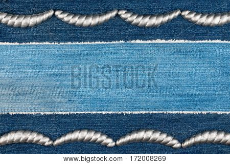 Luxury elegant frame made of silver stucco plaster lying on denim. Copy space. View from above