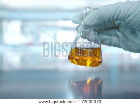 hand with orange solution in scientist hand with science laboratory background