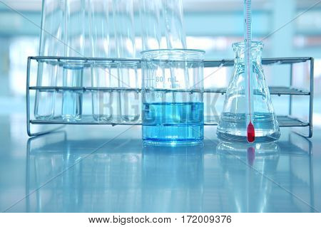 beaker and flask with blue water and thermometer in science laboratory background