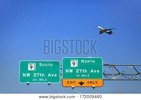 Signs on the road in Miami and the plane in the sky