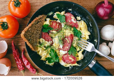 Fresh cooked scrambled eggs in pan with sausage and herbs. Bread fork vegetables on wooden board top view
