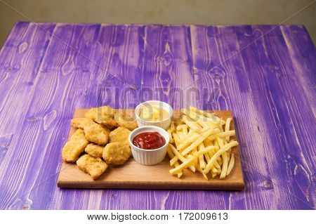 French fries chicken nuggets and two white cups with ketchup and cheese on a wooden Board lying on a painted purple wooden table with copyspace