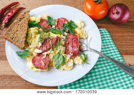 Fresh cooked scrambled eggs with sausage and herbs in white plate.Bread napkin fork vegetables on wooden board