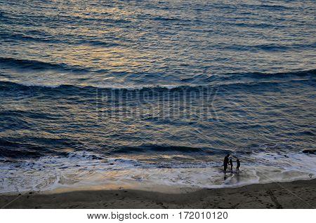 Father and two daughters testing the water at Playa Gaviotas in Mazatlan,Sinaloa,Mexico.