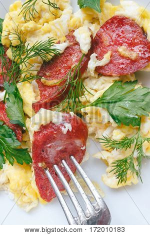 Fresh cooked scrambled eggs with sausage and herbs in white plate with fork