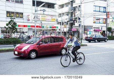 Traffic Road And Japanese People Dive Car And Biking Bicycle On The Road At Shinjuku City
