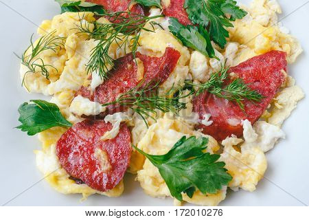 Fresh cooked scrambled eggs with sausage and herbs in white plate.