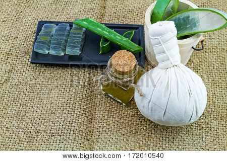 Spa compressing ball Fresh aloe vera gel on black ceramic dish with aloe vera essential oil and color pill on fabric sack