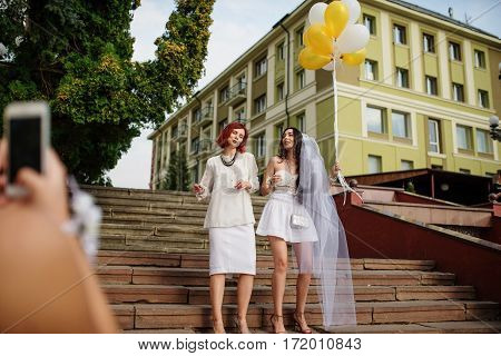 Two Girls With Balloons At Hand On Hen Party. Making Photo By Phone.